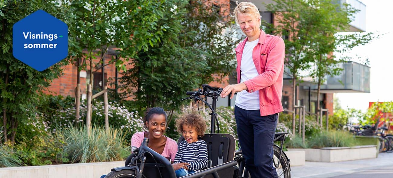 Smilende mann som holder sykkel med kvinne og barn på vei til sommervisning.