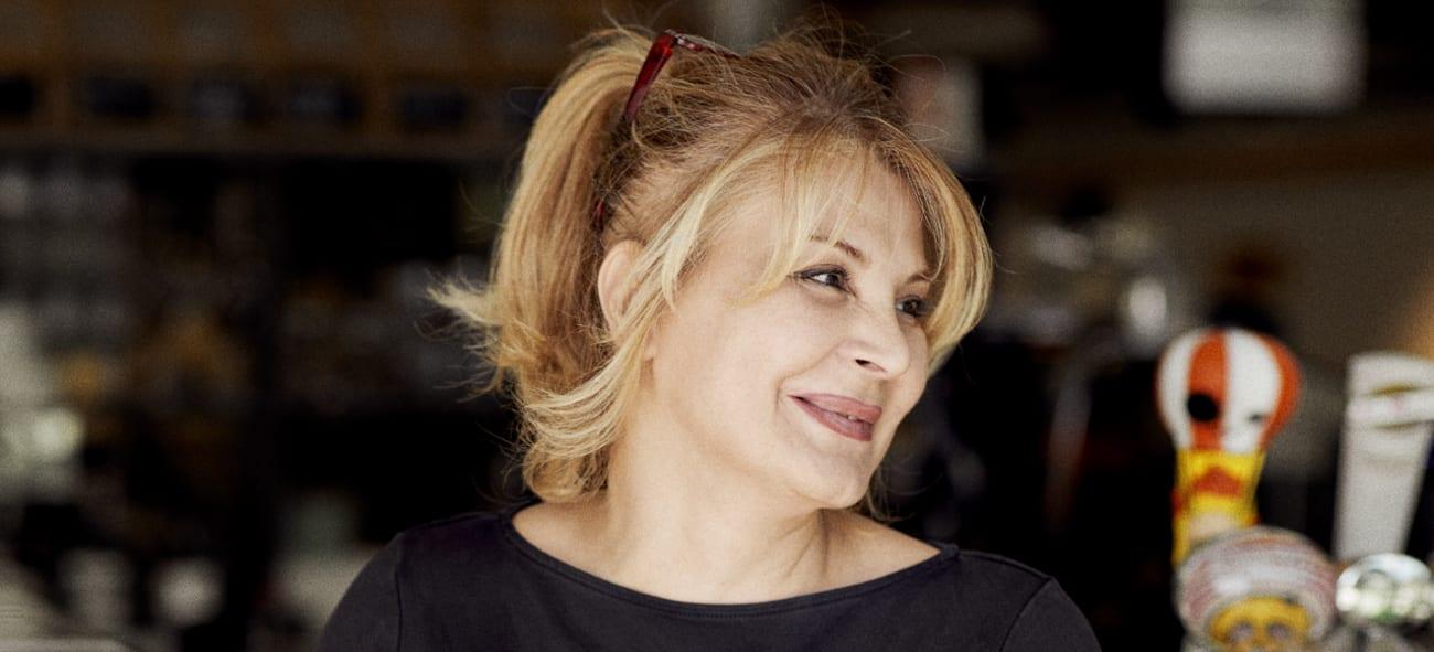 Blond kvinne som smiler og ser til siden på Ulven.