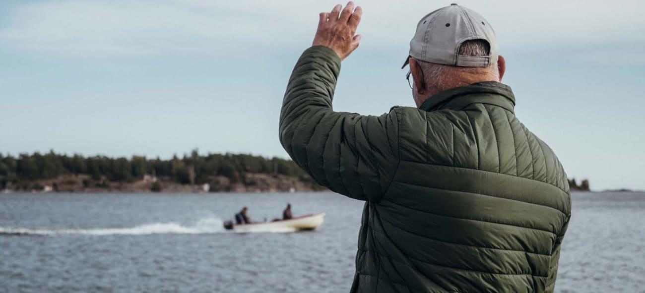 En man som vinkar åt en båt