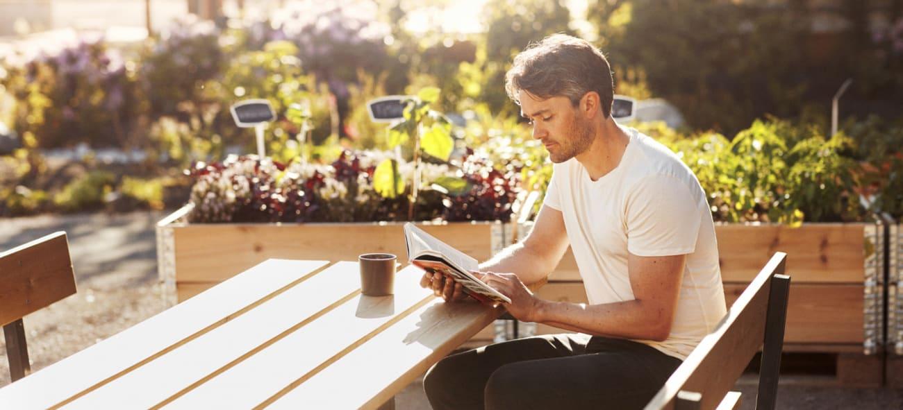 Mann som leser i bakgården på Ulven omringet av fulle plantekasser.