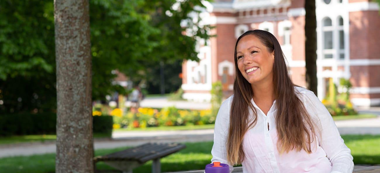 Smilende kvinne som sitter i en park med en kaffe.