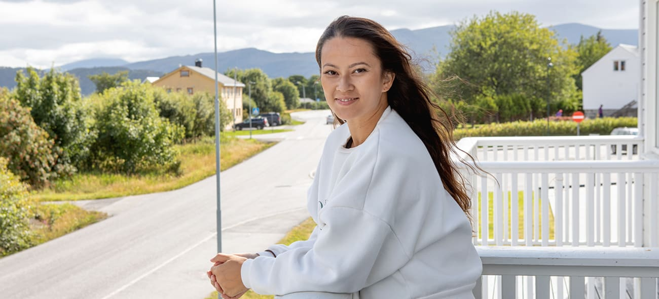 Kvinne i hvit genser står på en balkong