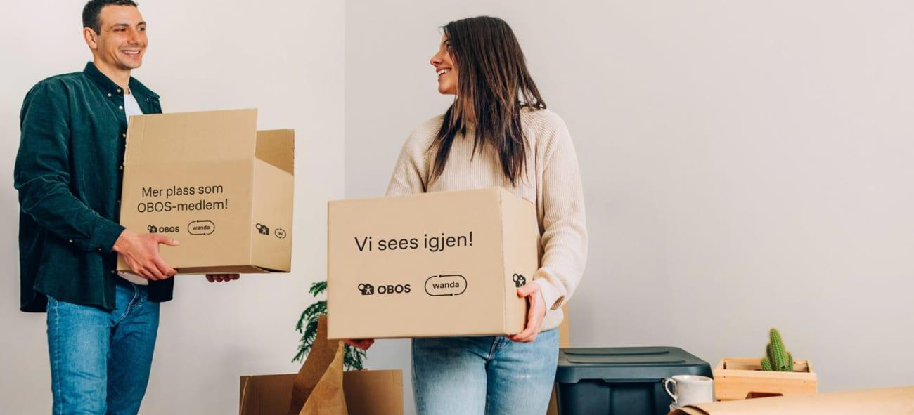 Mann og kvinne i en stue som holder hver sin pappeske