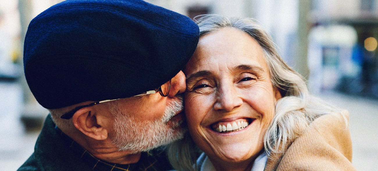 Et eldre par hvor mannen koser kvinnen på kinnet.
