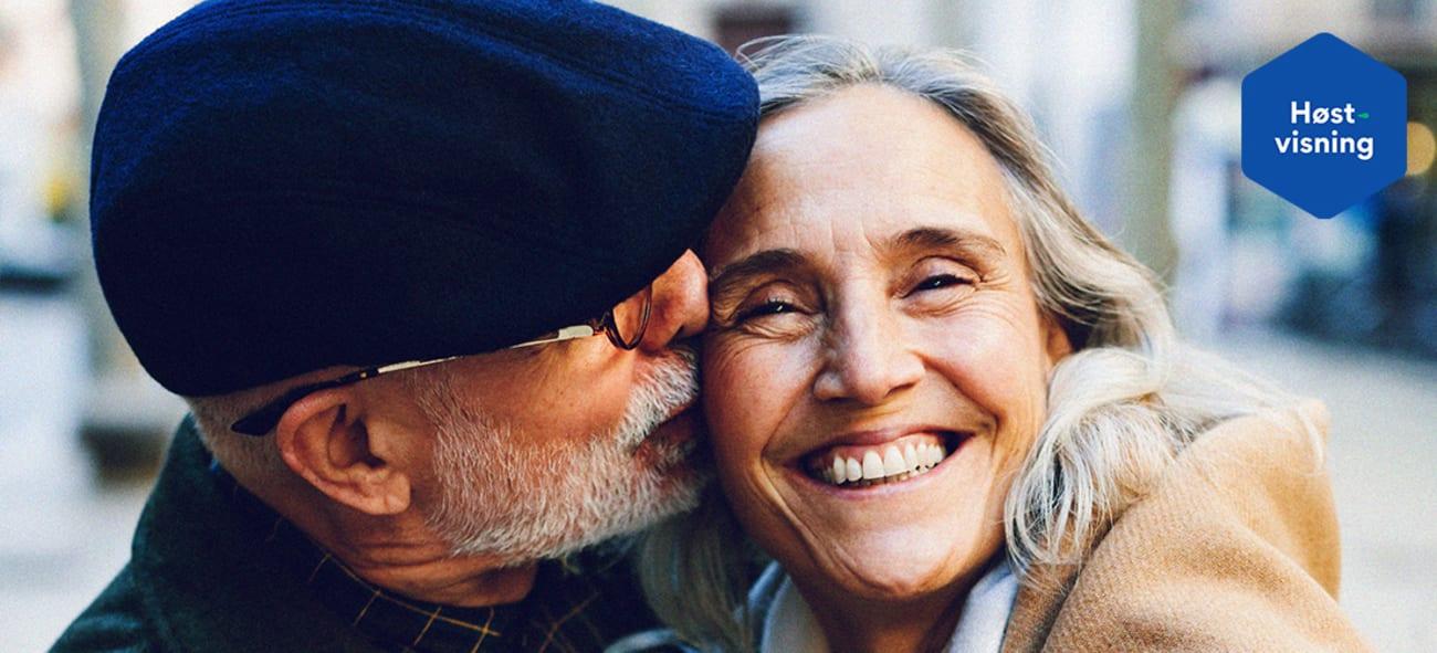 Et eldre par hvor mannen koser kvinnen på kinnet med logo.