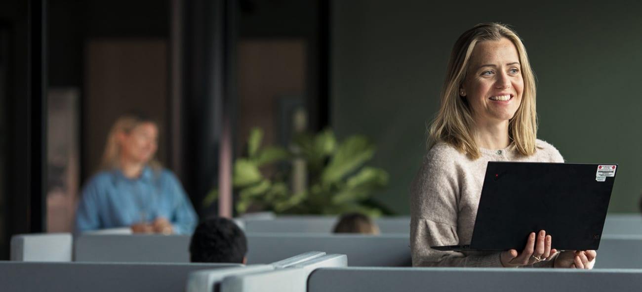 Dame smiler med PC i hånden på et OBOS nærkontor