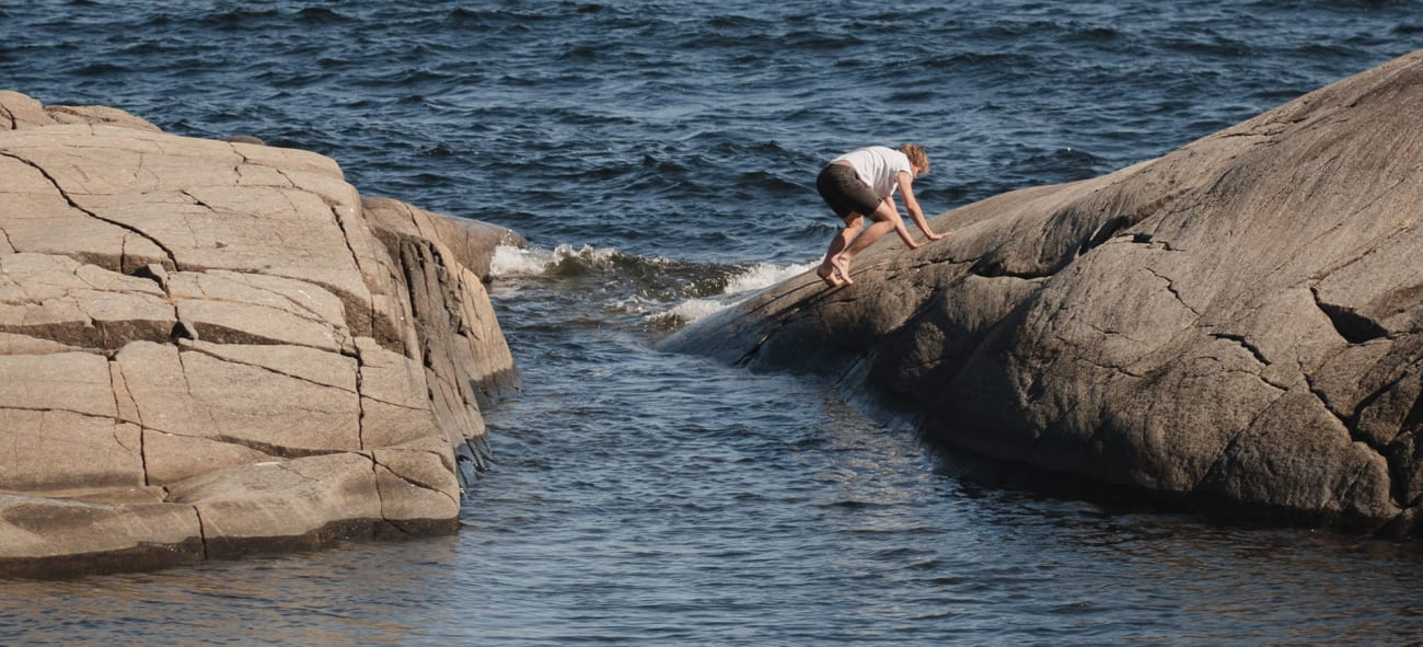 kille som klättrar på klippor