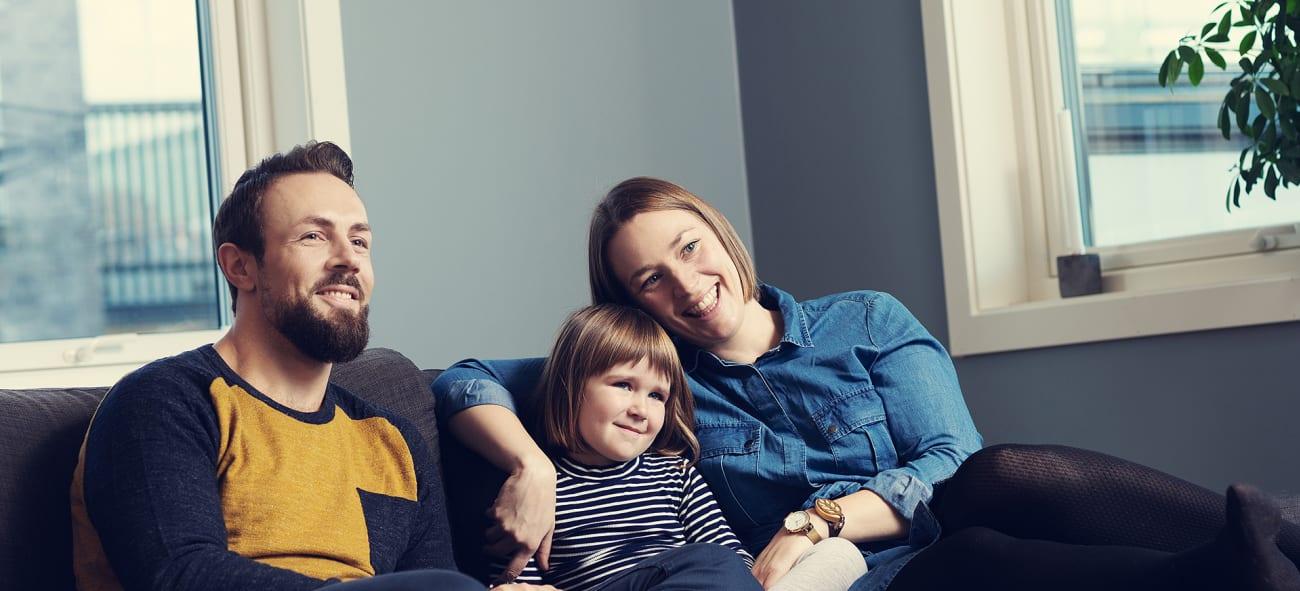 en familj sitter tillsammans i en soffa