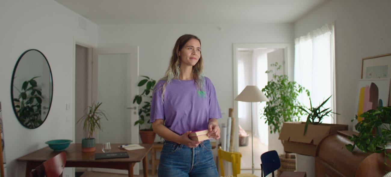 Dame i en lilla t-skjorte som smiler i egen leilighet.