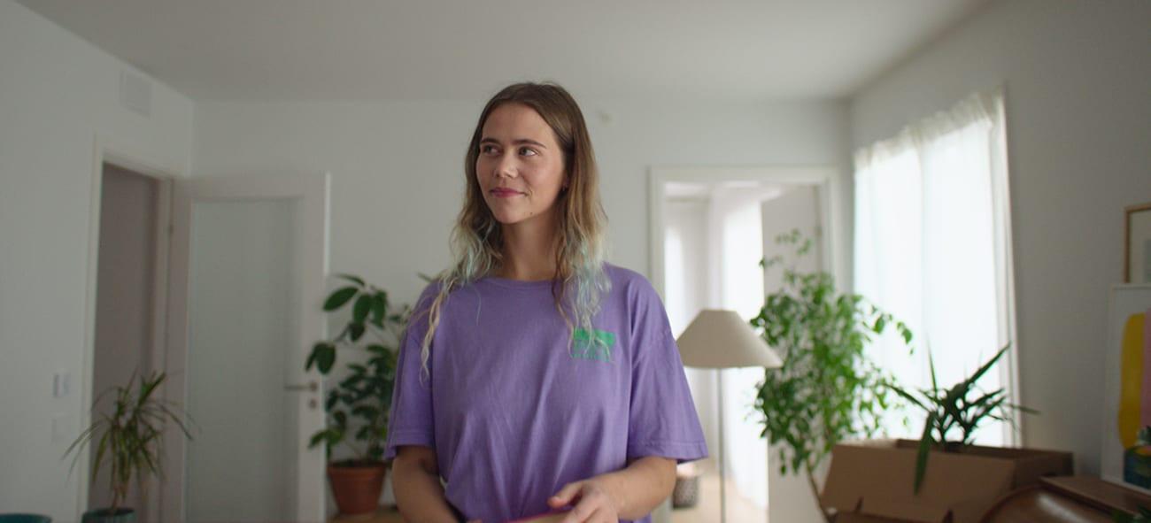 Dame i lilla t-skjorte som holder noen bøker.