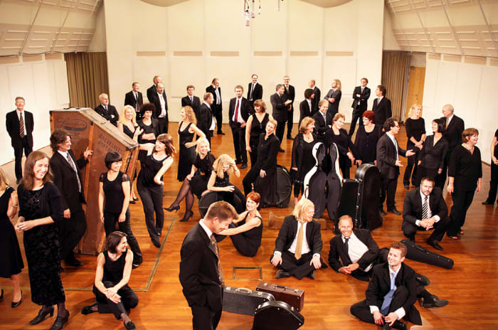 Hele orkestret samlet: Noen sitter og andre står. Damene er kledd i svart kjole og herrene i dress.