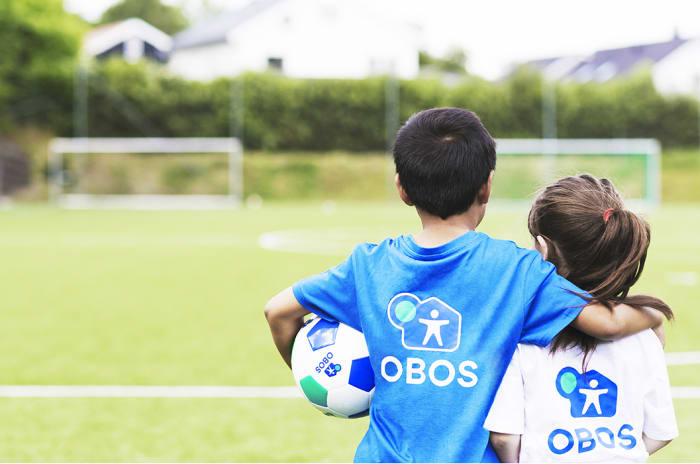 En gutt og en jente på fotballbane med OBOS-logo på ryggen.