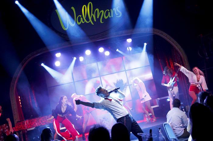 En mann synger i en mikrofon med dansere bak.