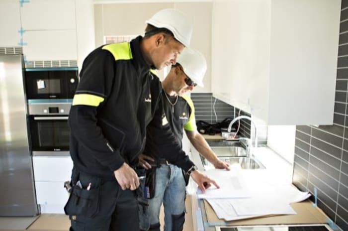 To elektrikere står på et kjøkken og ser på en plan