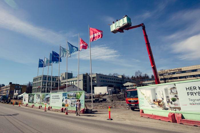Bilde fra byggeplassen hvor Frysjaparken bygges. Bildet viser lift på byggeplassen samt skilter og flagg.