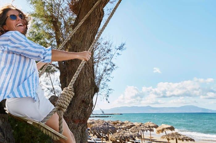 En kvinne på en huske ved en eksotisk strand