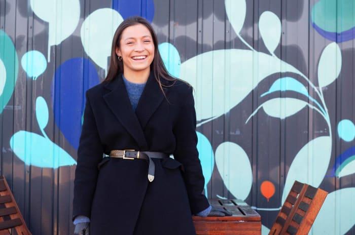 Bilde av Madeleine Slorbak smilende foran en fargerik vegg
