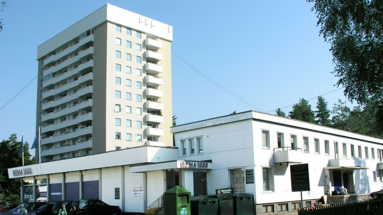 Bilde av Vetlandsveien 68-100. Hvitt firkantet butikklokale med høyblokk i bakgrunnen.