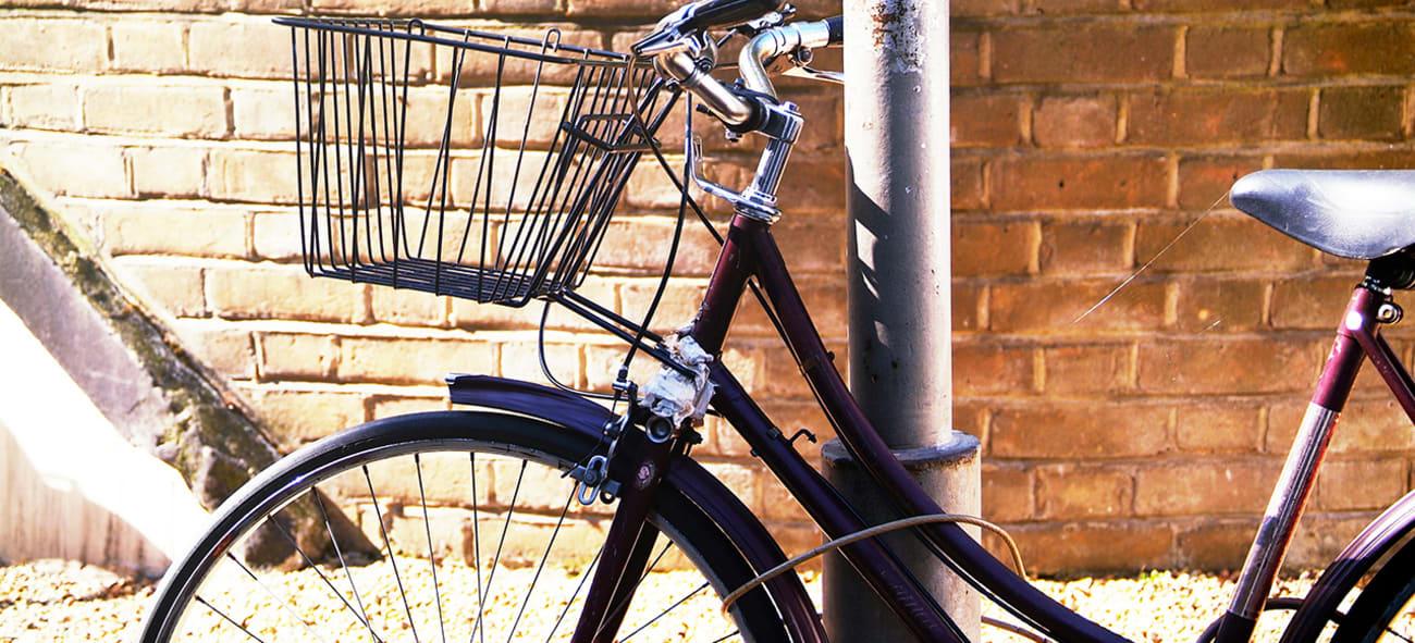 En svart damesykkel låst til en lyktestolpe.