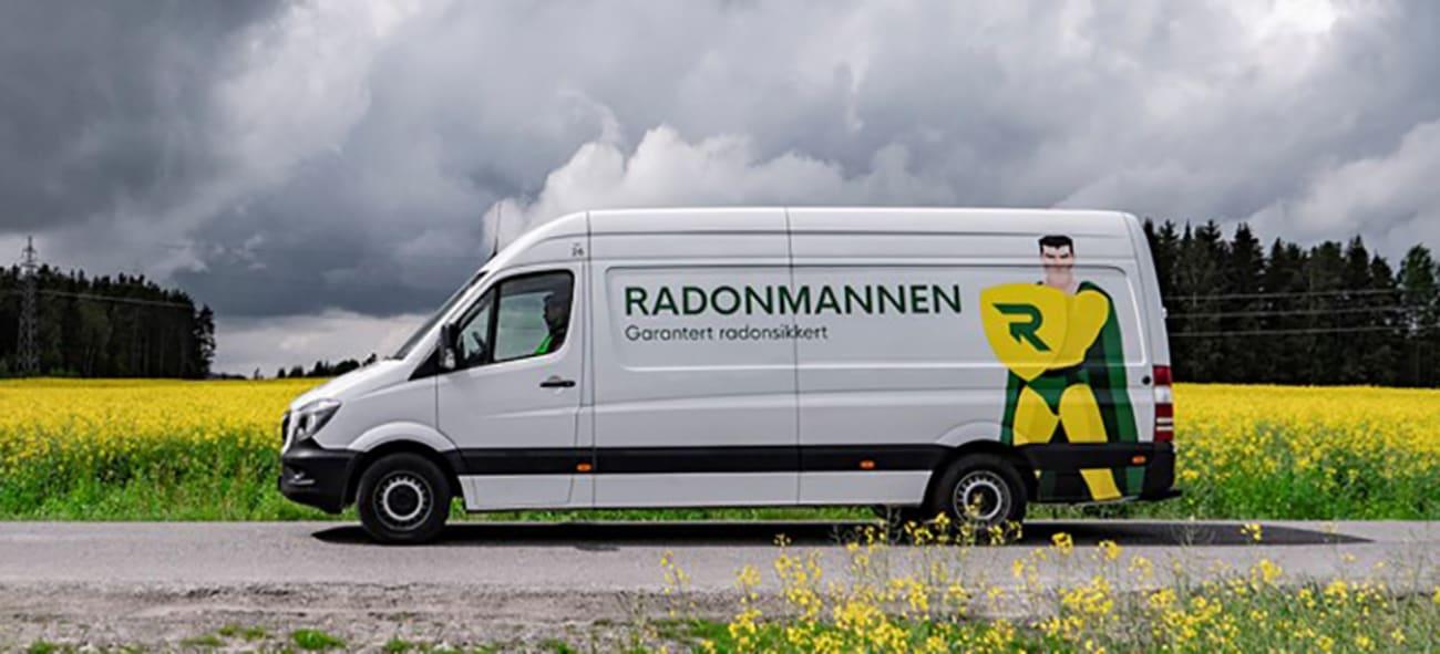 En bil med Radonmannen logo kjører forbi en eng.