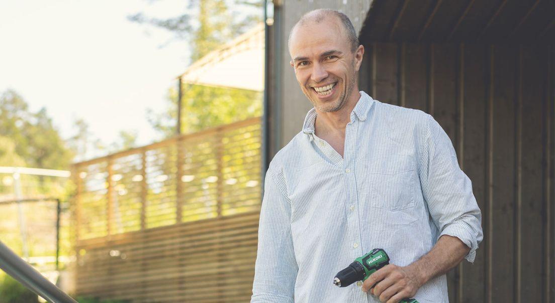 Smilende mann med en drill i hånden