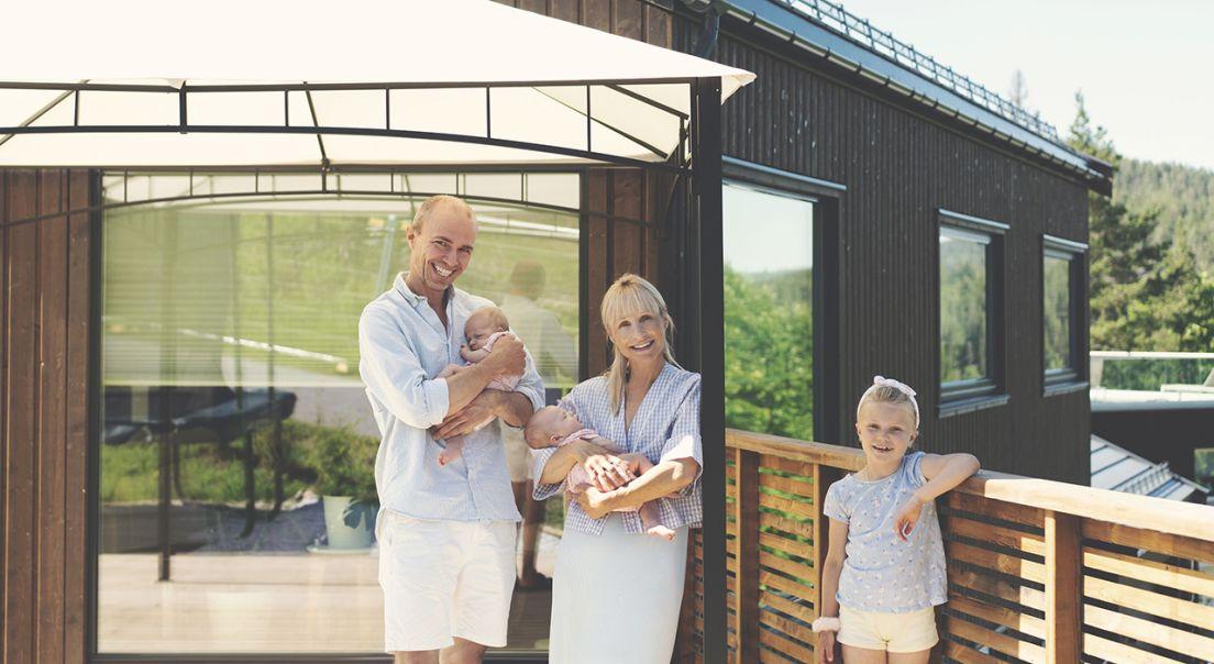 Smilende familie på fire på terrassen