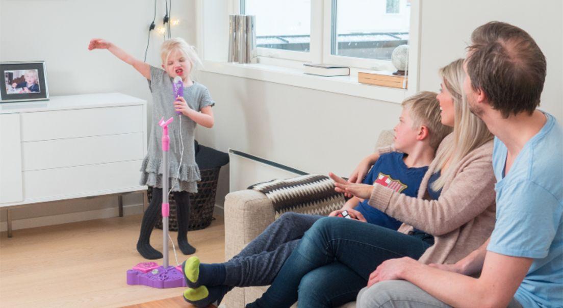 En jente synger i en lekemikrofon foran resten av familien i stuen.