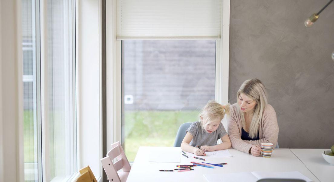 En jente sitter ved kjøkkenbordet og tegner, mens mor sitter ved siden av og ser på.