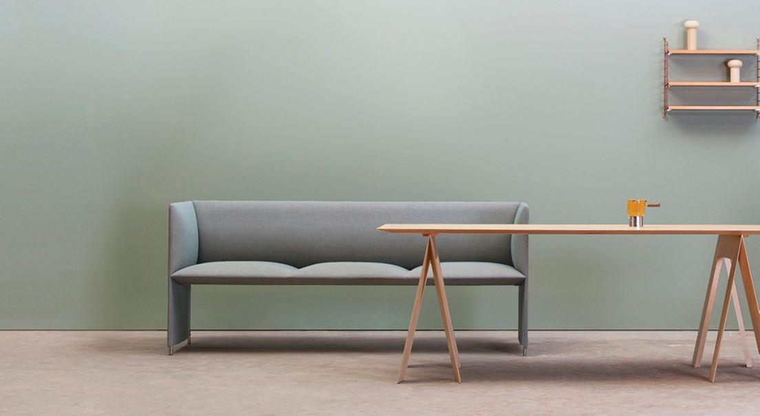 Minimalistisk rom med en sofa, et bord og en hylle på veggen
