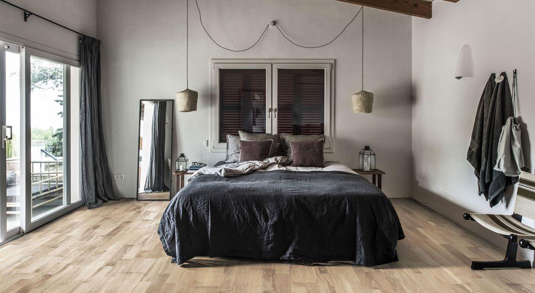 Bilde av et soverom med en stor seng midt i rommet med sort sengeteppe.