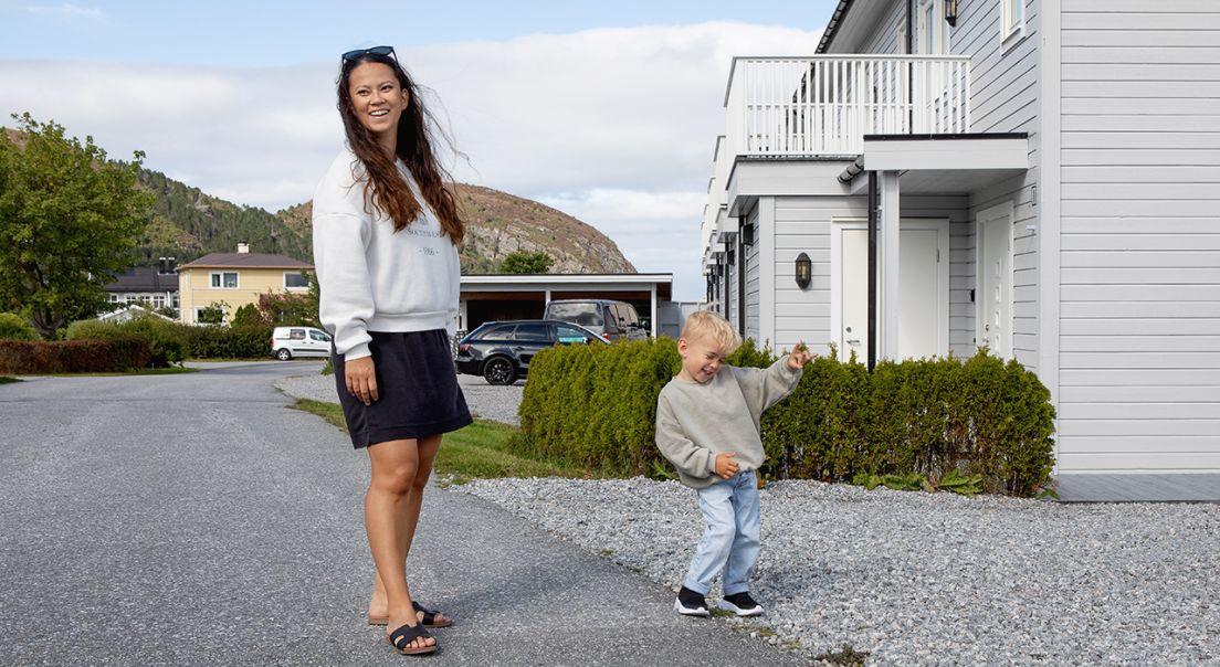 Smilende mor og sønn står foran et hvit hus