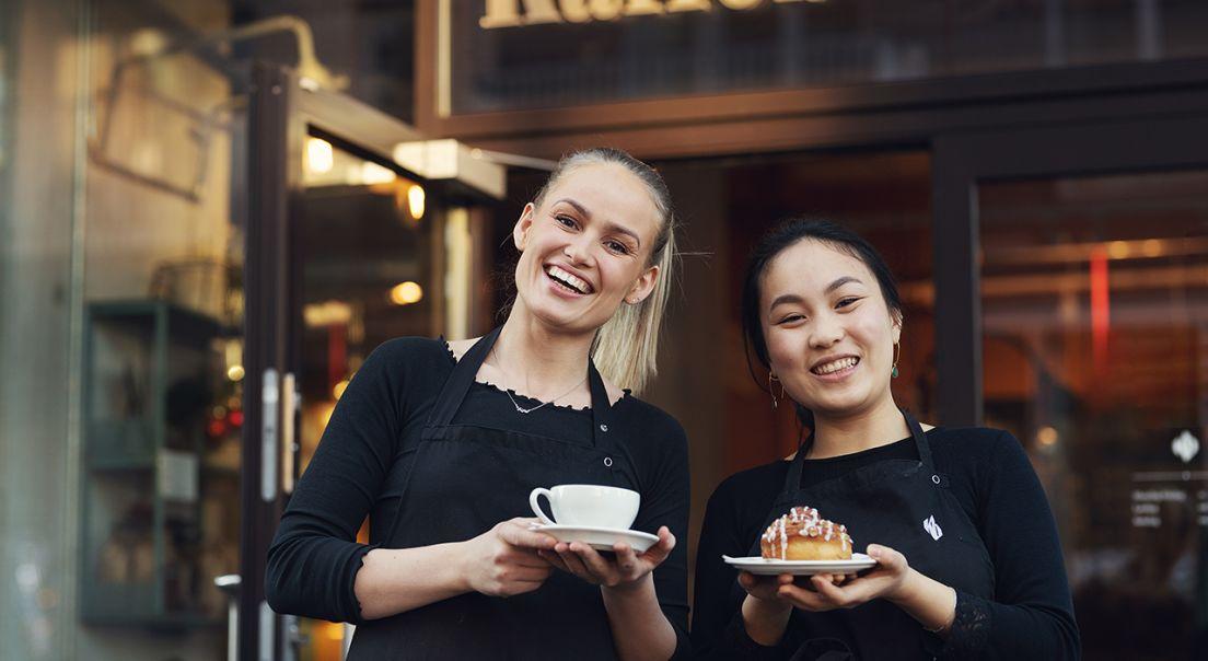 To baristaer står utenfor Kaffebrenneriet med kaffe og bakverk