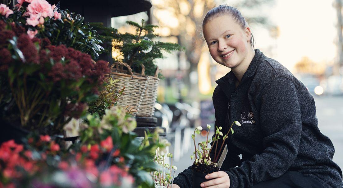 Kvinne i blomsterforretning smiler til kamera