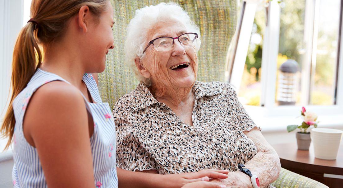 Eldre dame som holder barnebarnet sitt i hånden