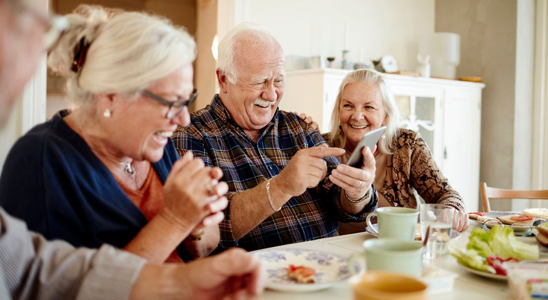 Eldre som ler og hygger seg rundt spisebordet