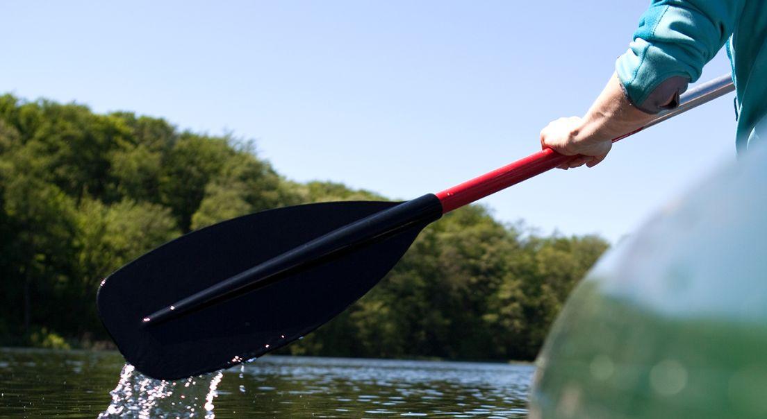 Bilde av en mann som padler i kano.