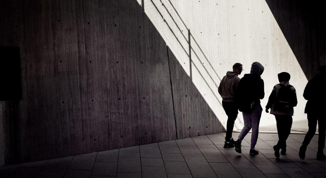 Ryggen til fire ungdommer som går i en undergrunn av betong.