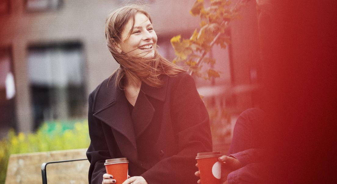 Kvinne på en benk med en kaffe som smiler på Ulven.