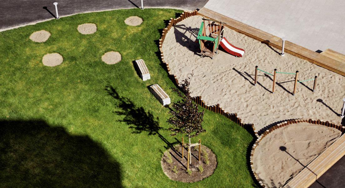Dronebilde av grønt området og lekeplassen på Ulven.