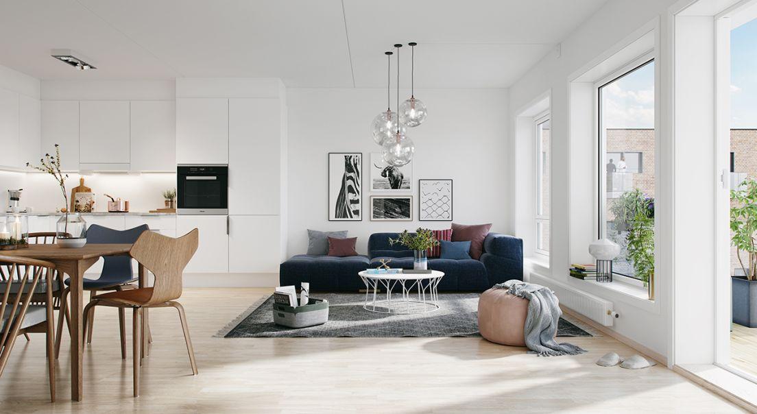 Lys stue med mørk sofa, hvitt kjøkken og trespisestue