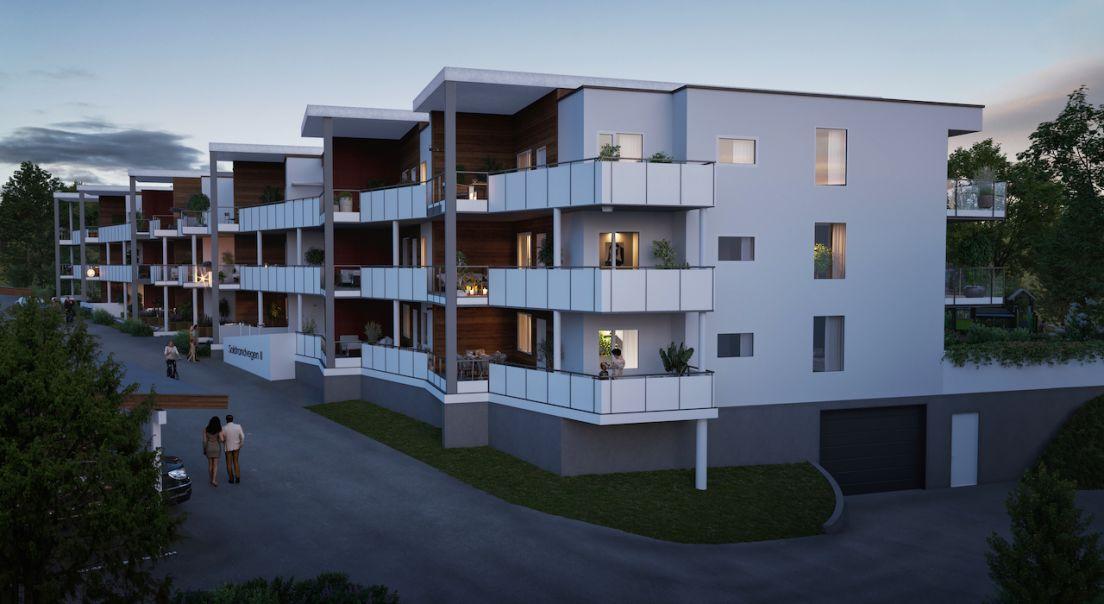 Illustrasjon av boliger i Solstras-prosjektet i tre etasjer, verandaer og underjordisk garasjeanlegg.