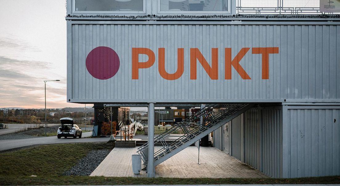 Bilde av samlingshuset på Punkt på Fornebu. På veggen står det Punkt med store bokstaver.