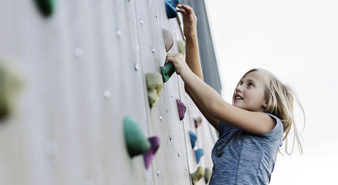 Bilde av et barn som leker i klatrevegg på Fornebu