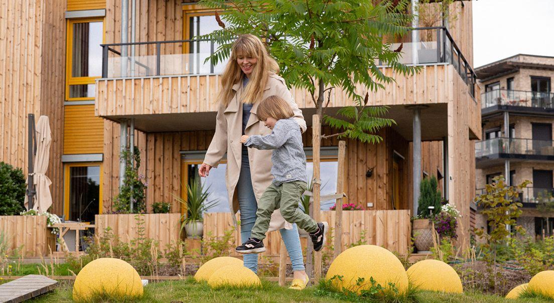 Mor og sønn leker på lekeplass på dagtid på Fornebu.