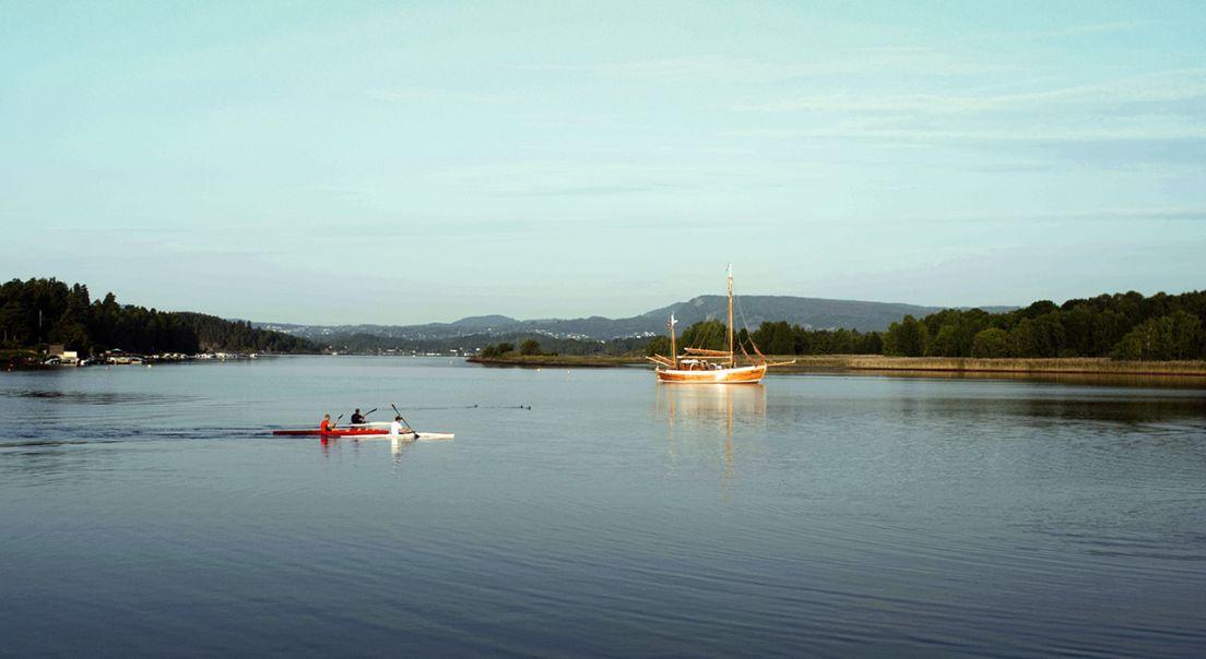 Vann med tre menn som padler kajakk med en båt i bakgrunnen.