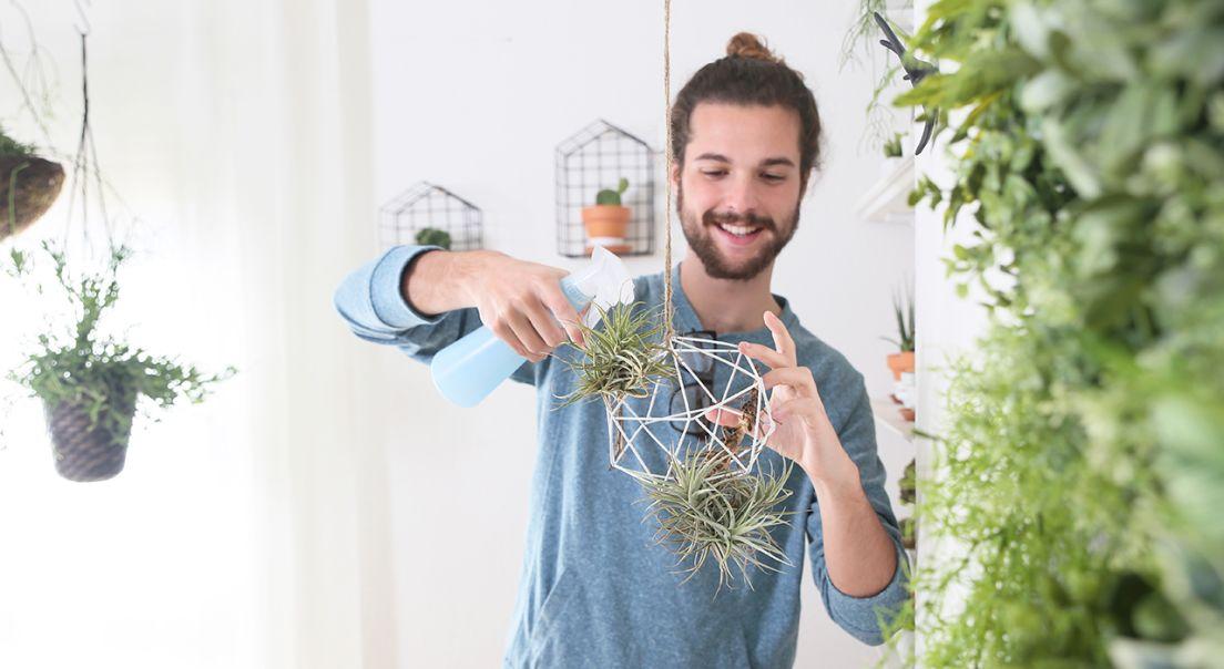Bilde av en ung mann som vanner planter i en leilighet