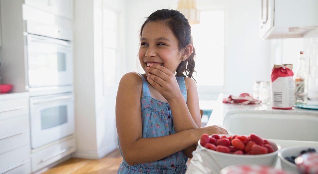 Bilde av en jente som smiler og spiser ferske bringebær på et kjøkken
