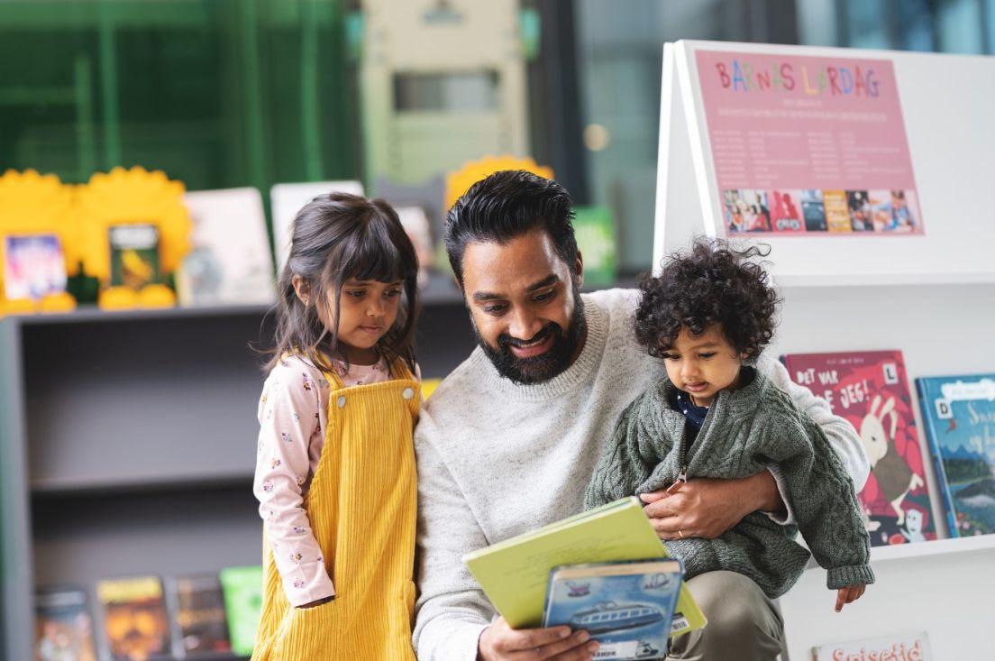 Illustrasjonsfoto av far med to barn på et bibliotek.