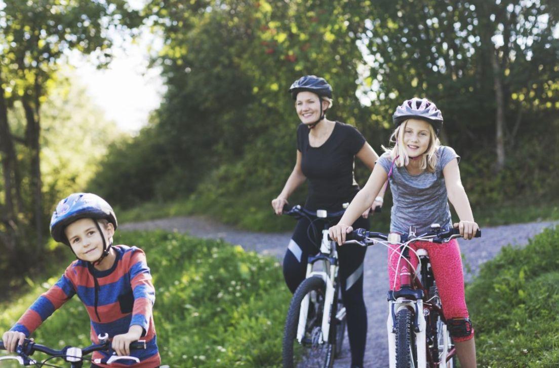 Illustrasjonsfoto av en mor og to barn på sykkeltur.