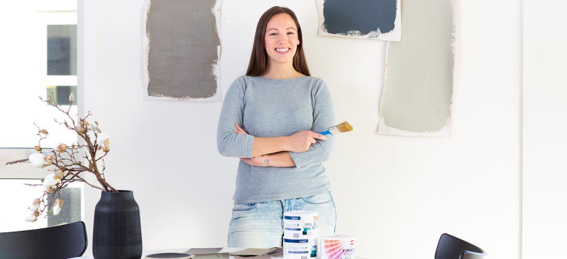 En ung kvinne foran en vegg med malingsprøver